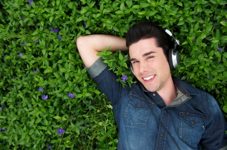 Portrait of an attractive young man lying on grass listening to music on headphones photo