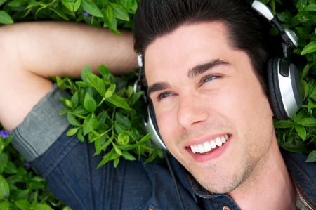 Close up portrait of a happy young man relaxing with headphones photo
