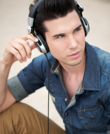black hair blue eyes: Close up portrait of a handsome young man listening to music with headphones Stock Photo