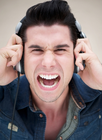 Close up portrait of a young man shouting with headphones photo