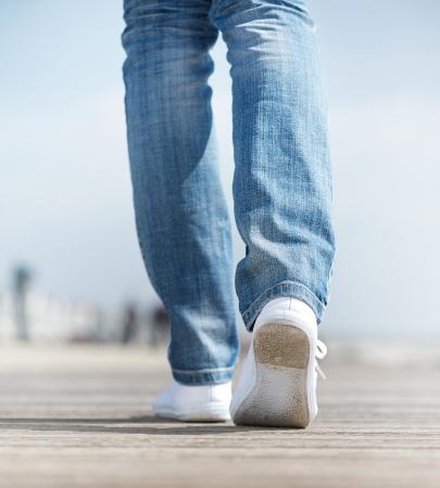 屋外快適な白い靴を歩いて女性のクローズ アップ 写真素材