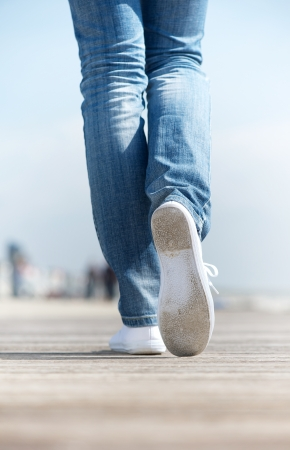 Close up portrait of a woman walking outdoors in comfortable white shoes photo