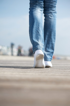 Rear view portrait of a woman walking in blue jeans and comfortable white shoes photo