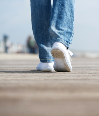 Close up rear view portrait of a woman walking in comfortable white shoes outdoors photo