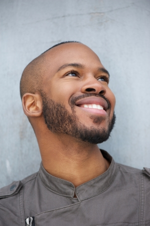 Close up portrait of a happy young african american man smiling and looking up photo