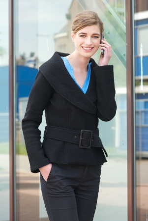 Portrait of a happy business woman walking and talking on mobile phone outdoors photo