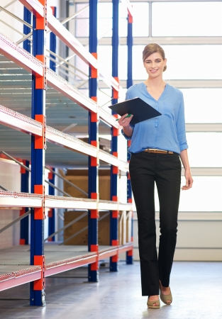 Happy businesswoman standing in next to shelves in warehouse with clipboard photo
