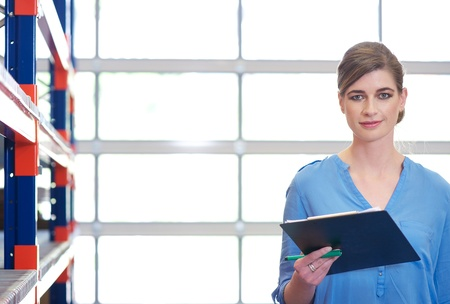 Close up portrait of a businesswoman with clipboard in warehouse Stock Photo - 20146883