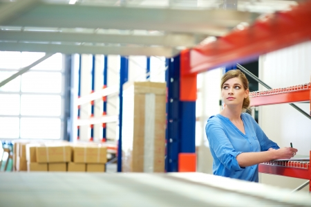 Portrait of a business woman inspector doing inventory in a warehouse Stock Photo