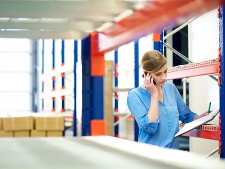 inventario: Retrato de una mujer de negocios en el teléfono y verificar el inventario en almacén
