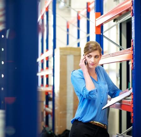 inventory: Retrato de un empleado de log�stica femenina en el tel�fono y el control de inventario en almac�n