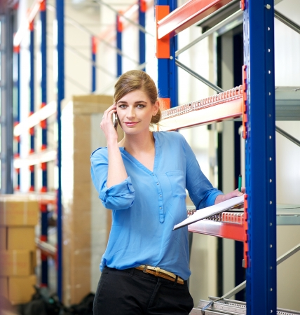 Portrait of a businesswoman talking on mobile phone in warehouse photo