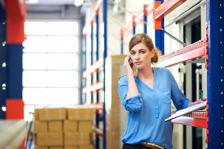 Portrait of a female logistics worker on mobile phone in warehouse photo