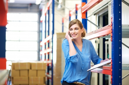 Portrait of a female logistics worker controlling stock and talking on cellphone in warehouse photo