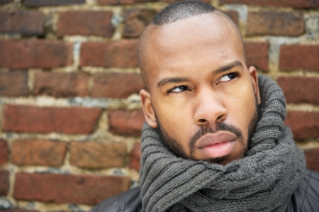 Portrait of a young african american man with gray scarf looking up photo