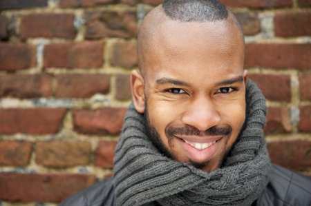 Close up portrait of a happy african american man smiling with scarf outdoors photo