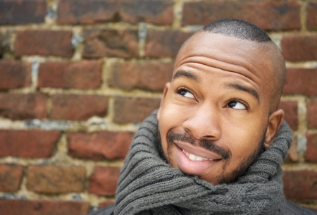 Portrait of a handsome young man smiling with scarf outdoors photo