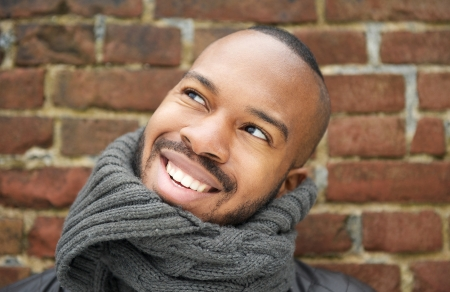 Close up portrait of a happy young man smiling outdoors with gray scarf photo