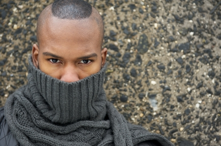 Close up portrait of an african american male fashion model with gray scarf covering face photo