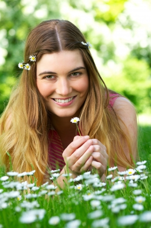 Portrait of a beautiful young woman holding flower in the park photo