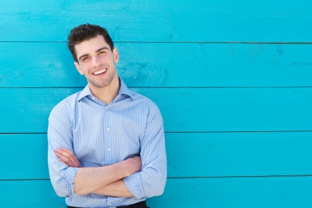 Close up portrait of a handsome young man smiling with arms crossed Stock Photo