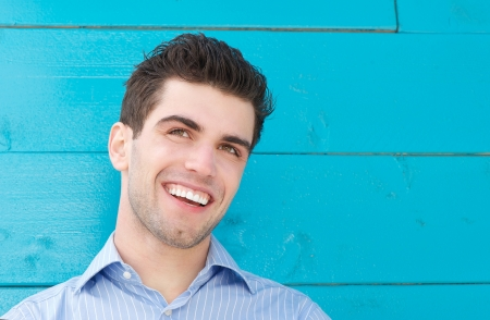 Close up portrait of a handsome young man smiling and looking away photo