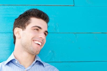 Close-up portret van een knappe jonge man glimlachend en op zoek weg