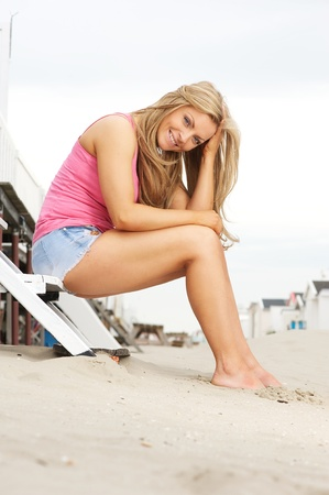 Portrait of a cute young woman smiling at the beach photo