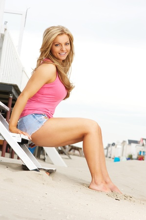 sexy shorts: Portrait of a beautiful young blond woman sitting barefoot at the beach