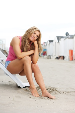 Portrait of a beautiful young woman sitting at the beach with barefeet in sand photo