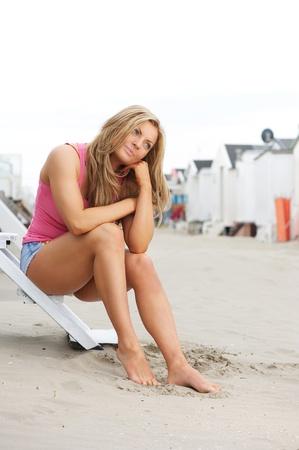 shorts: Retrato de una joven y bella mujer sentada en la playa con los pies descalzos en la arena