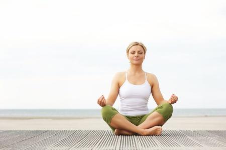 Portret van een mooie jonge vrouw zitten in yoga pose op het strand