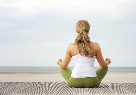 요가 포즈 해변에 앉아 젊은 여자의 후면보기 초상화