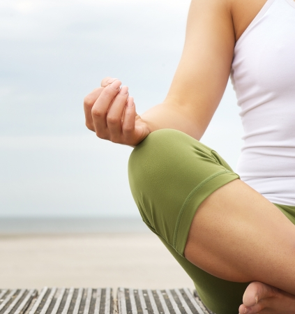 Close up portrait of a young woman in lotus position with yoga hands at the beach photo