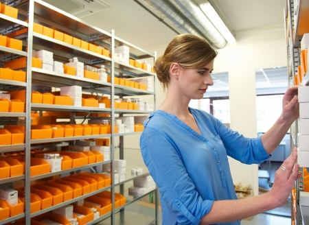Portrait of a young female pharmacist looking for medicine on shelves photo