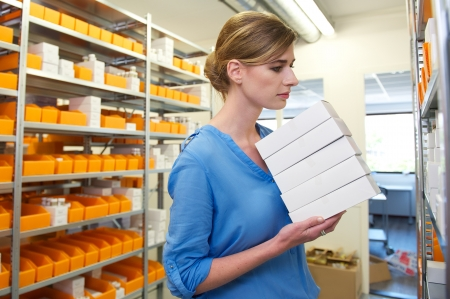 Young female pharmacist holding boxes and looking for medicine on shelves photo