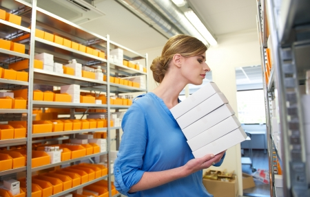 Young female pharmacist holding boxes and searching for medicine on shelves photo