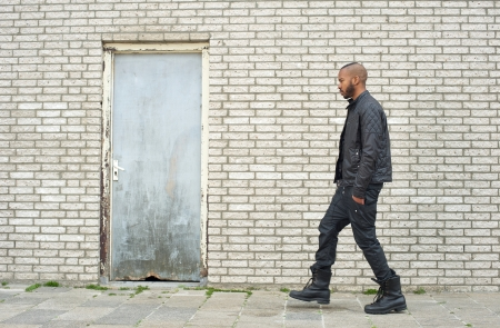 Portrait of an african american fashion model walking in urban environment photo