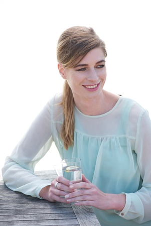 Close up portrait of a happy young woman enjoying a drink at a restaurant photo