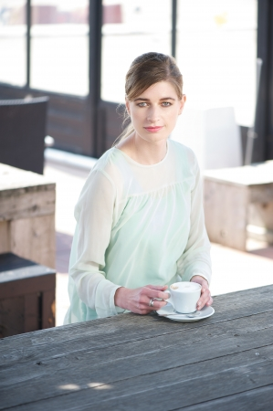 Portrait of an elegant young woman sitting at a table with a cup of coffee photo