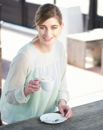Portrait of a cheerful young lady holding a cup of coffee outdoors photo