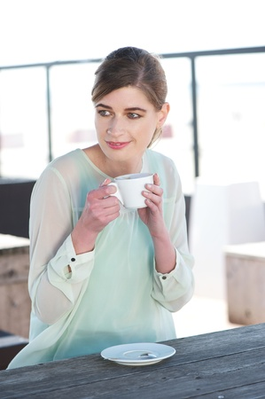 Portrait of a young woman sitting at a table outdoors and enjoying a cup of coffee photo