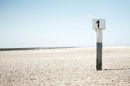 numero uno: Un puesto de la marea en la playa arenosa individual con el número uno Foto de archivo