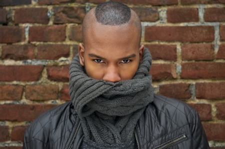 Close up portrait of a male fashion model with scarf covering face photo