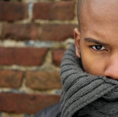 male fashion model: Medio retrato de la cara de un modelo de moda masculina atractiva con la cara cubierta de la bufanda Foto de archivo