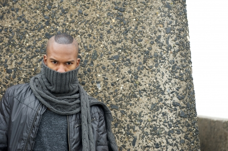 Portrait of a black man with scarf covering face outdoors photo
