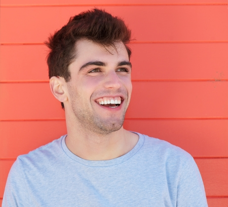 Close up portrait of an attractive young man laughing outdoors photo