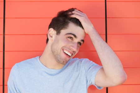 smiling young man: Portrait of an attractive young man smiling with hand in hair Stock Photo