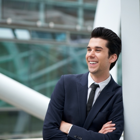 business buildings: Portrait of an attractive young businessman smiling outdoors