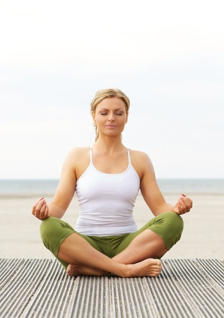 Portrait of a beautiful young woman sitting in yoga pose outdoors Imagens